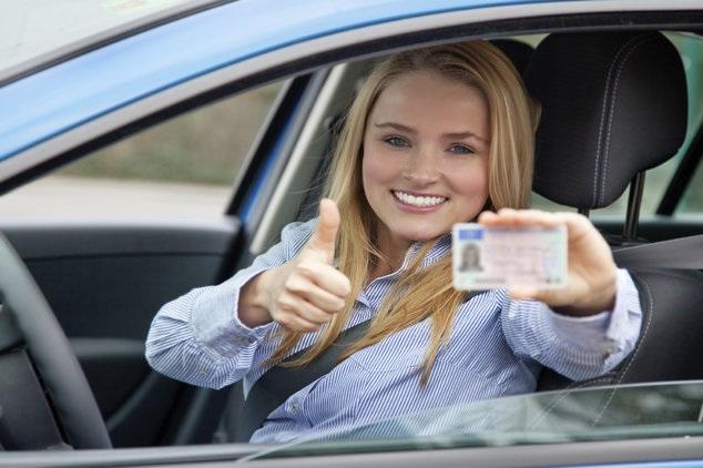 Donna al volante con patente in mano